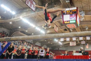 Sophomore Courtney Bisbe does a backflip split on the beam while her team watches. Bisbe scored a 9.675 during the four-school meet on Saturday. The Wolfpack placed third with a 194.050 behind WVU and UNC but ahead of William and Mary on Saturday in Reynolds Coliseum. By: Nick Faulkner