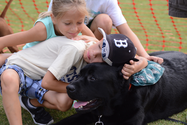 Paige and Jonas Birkhead sit with their dog Bear, an English black lab, outside of the competition ring at the Dog Olympics. Paige and Jonas's father, David Birkhead, brought Bear to the charitable event hosted on the College of Veterinary Medicine campus on Saturday, September 10, 2016.