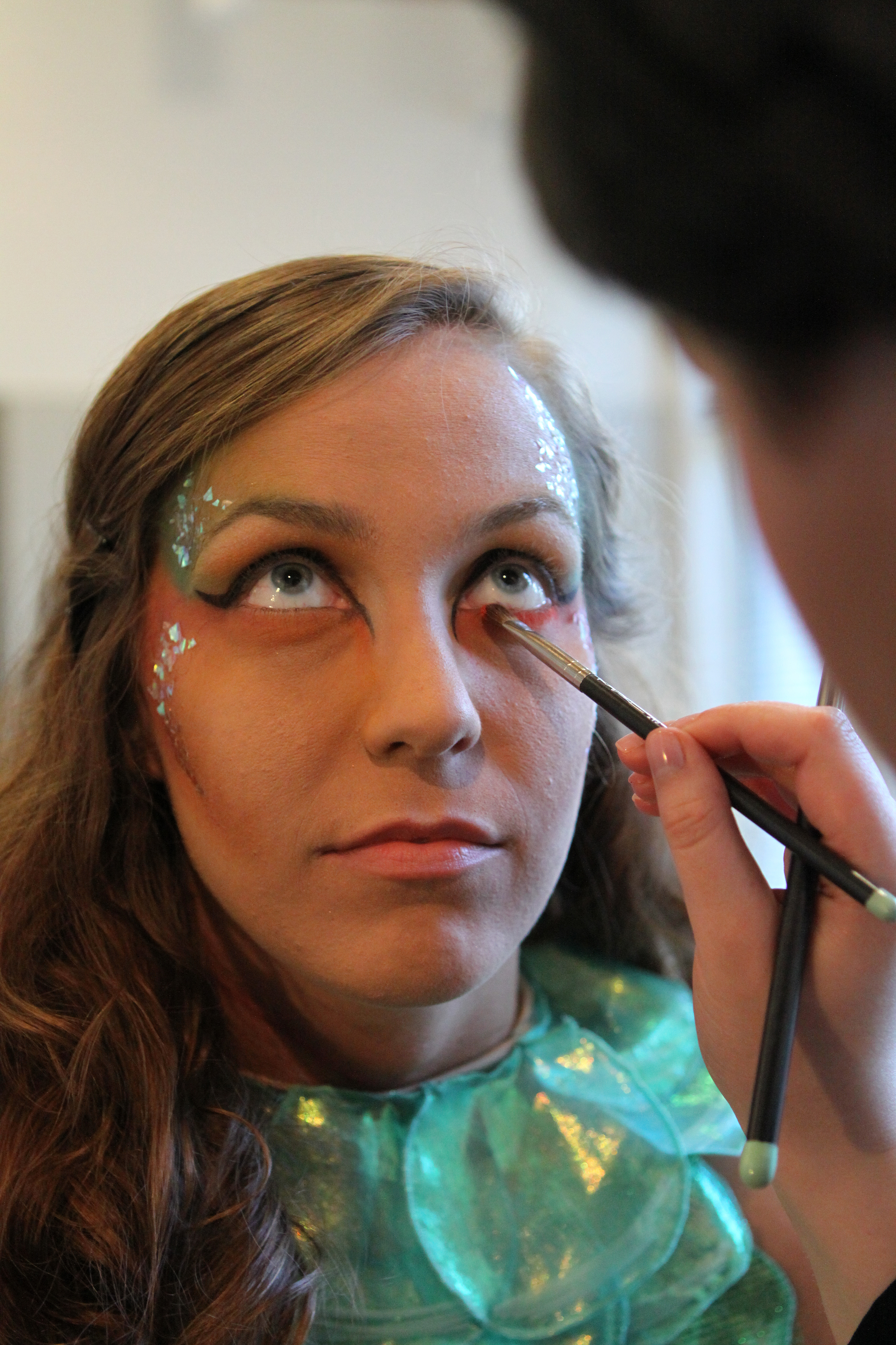 "Photo by Joannah Irvin. Elizabeth Rich, a model in Art to Wear, gets makeup applied during the preshow routine. Rich was a model in the ""Creatures of the Deep"" collection designed by Sarah Edens and Lindsey Sherrill, a junior and a senior in fashion and textile management."