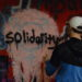 Person spray painting solidarity over transgender symbol
